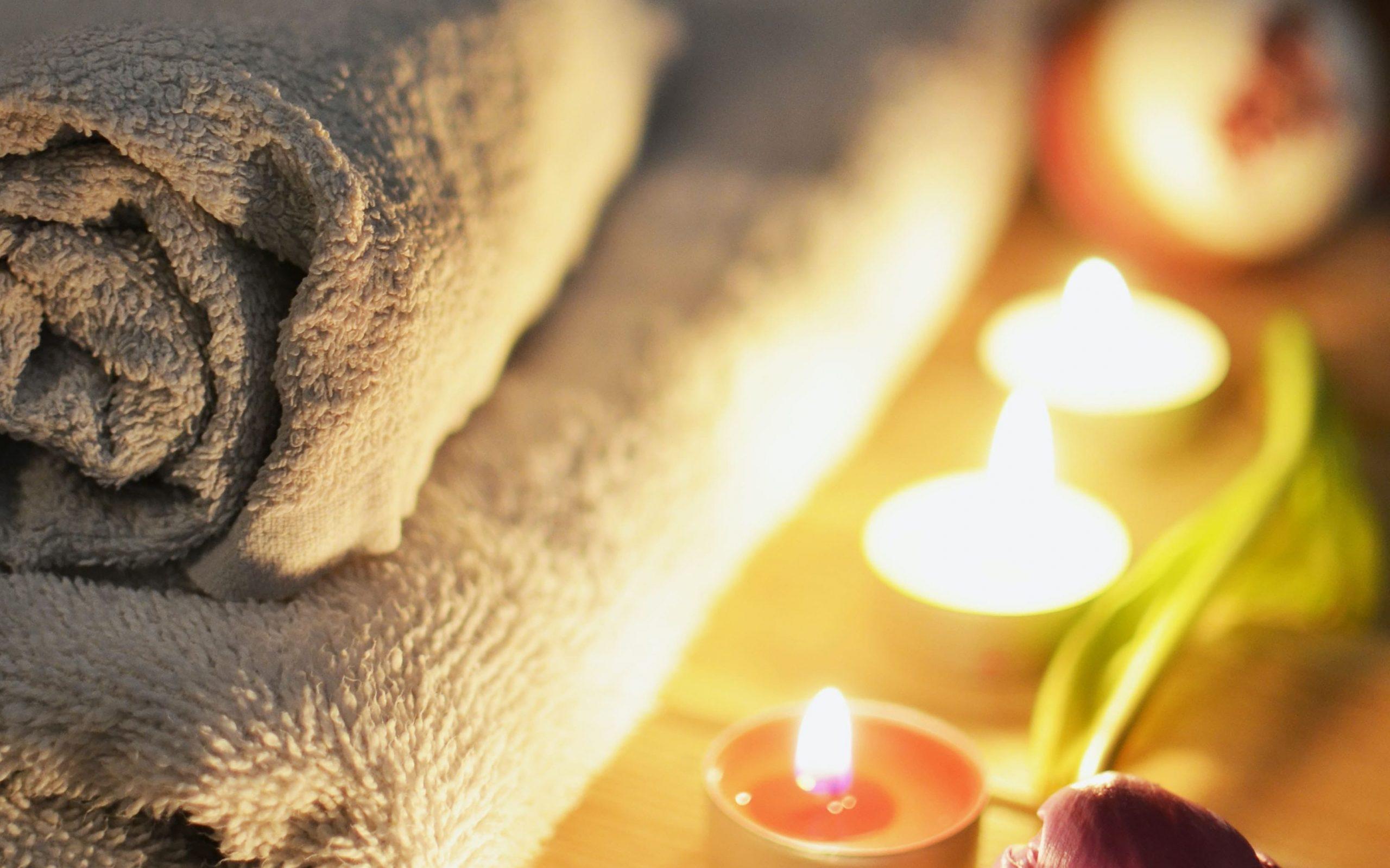 Serviette chaude pour un massage détente dans une ambiance tamisée avec des bougies colorées et odorantes